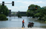 Jim Spoonamore, checks out the flooding in downtown while visiting his sister in Davenport, Iowa.,...