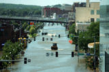 A piece of heavy machinery drives down a flooded street in downtown from the Mississippi River in...