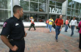 Alex Paez (cq) of the Denver Fire Department watches as employees of 1670 Broadway pour onto the...
