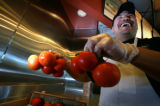 using vine ripened tomatoes for their fresh salsa at  Qdoba in Denver, Colo. on Monday, June 9,...