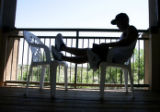 Brian Aragon (cq) reads a book on the balcony of his apartment, at Lambertson Farms Apartmentrs,...