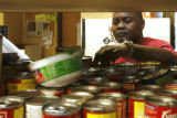 DM0045  Volunteer Gregory Thomas sorts through cans at the Jeffco Action Center Monday Nov. 24,...