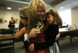 MJM653  Case worker, Ashley Scritchfield (cq), center, hugs Alice Mendoza, 5, left, and her...