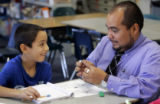 4th grade teacher Juan Osorio, translates a paragraph structure writing lesson to Anthony Perez at...