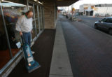 MJM570  Olympic Stationers employee, Steve Hagar (cq) vacuums outside the store in downtown Port...