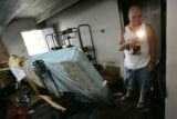Maintenance man James Meisenheimer (cq) shines a flashlight on damaged areas in apartment 202 of...
