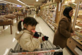 Nour Al Saad, 3, eats a free cookie at King Soopers while her mother, Soud Al Taai does the...