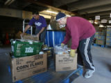 Greg Fischer (cq) left, and Robert Roth (cq), pantry operator, check in food at the warehouse,...