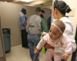 Glenis Santos (cq) and her 6 month old daughter, Kristal Padilla, wait in line to pick up some...