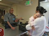 Aubrey Knight, (cq) volunteer, left, helps Glenis Santos (cq) and her 6 month old daughter,...