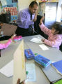 4th grade teacher Juan Osorio, high fives student Julisa Garcia for being the only person at her...