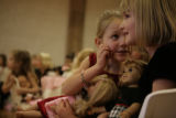 Eva Derksen, 7, left, talks to Allee Burke, 7, right, during the Annual Oxford Dolls' Tea Party at...