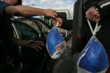 A man hands  a turkey off to a mission worker Sunday, November 23, 2008. The Denver Rescue Mission...
