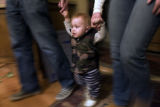 10-month-old Lasse Gaxiola walks between his mother, 3-time Olympian Sarah Schleper, and father...