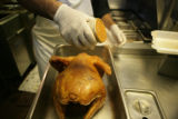 Agustin Garcia (cq) season's a turkey in the kitchen at Bayou Bob's, 1635 Glenarm Place in Denver...