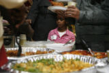 DM0467  LaLa Ali, 6, a refugee from Somalia looks over dishes as she makes her way down the food...