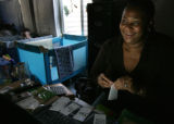 Sunjia Brown works on some name tags and smiles as Tyree May (in background) is the first to...
