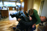 MJM298  Tracy Keil helps her husband, Matt Keil (cq) adjust in his wheelchair at their Parker,...
