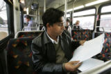 Som Baral, a 30 year old refugee from Bhatan, studies the bus routes as he rides one of two buses...