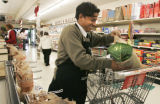 Som Baral, a 30 year old refugee from Bhatan bags groceries at King Soopers on Colorado and Ohio ...