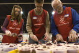 (0023) Volunteers dish out cranberry preserves shortly before a Thanksgiving dinner provided by...