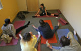 Marissa Manriquez (cq), top, leads a group of residents in a stretch class at a SPAN shelter,...