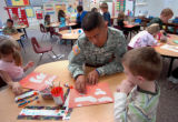 Staff Sergeant Carlos Barreto works with school children at Patriot Elementary School at Fort...