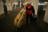 Tom Severino (cq) of Aurora, carries his string bass as he leaves the Denver International Airport...