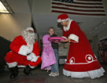 Santa Claus ( Pat Reynolds- cq) and Mrs Claus ( Marcela Rivera -cq),right,  offer cookies to 6...