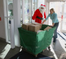 Aimee Caldwell-George (cq), right, gets some help with the door from to Santa Claus ( Pat...