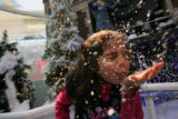 MJM661  Vanessa Rodriguez, 6, of Mountain View Elementary of Longmont, Colo. blows fake snow...