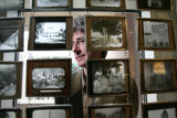 Creative Director Lonnie Hanzon peaks through a curtain of magic lantern slides on display at the...