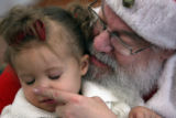 MJM264  Santa Claus played by Richard Gibboney (cq) touches the nose of Carlie Perez-Mesa, 2, as...