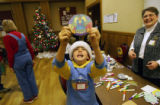 (0078) C.J. Hirsch (cq), 10, holds up an angel sun-catcher, during Family Christmas Crafts at...