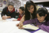 Alma Garcia, center, 12 helps Jennifer Pena, 9 right,  with her homework  after school at...