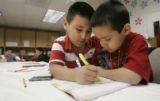 3rd grader David Lopez, 8, left helps Mathew DeSantiago, a 1st grader,  right, with his ...