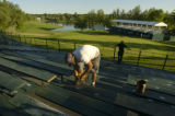 A worker secures floorboards on bleachers at the 18th green Tuesday evening, June 14, 2005,  at...
