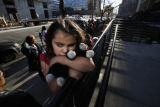 SR(027) Nine-year-old Yani Re Alvarado of Denver snuggles up to her toy cat Cop while she waits in...