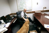 "State Treasurer Mike Coffman pets his dog ""Buckley"", a Golden Retriever, in his office..."