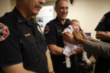 SR(093)  Littleton fire fighter Roxy Ligrani gingerly holds 9-week-old Sara Miller, the...