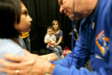 0409 Lourdes cruz, holds her son Joey while pediatrician Norm Scott, right,  gives Johanna, 7, a...