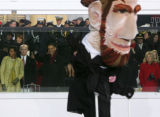 (0928) President Barack Obama waves to the crowd as a paper-mache Abraham Lincoln goes by the...
