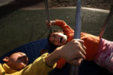 (PG14567) Siblings Juan Duran, 7, and Amy Duran, 6, laugh while spinning on the playground at...