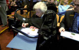 Chief Justice Mary Mullarky signs official certificates on her walker for Bernie Buescher ...
