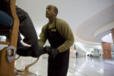 DM0013  Greg Perry shines shoes in the lobby of the Independence Plaza in Denver Tuesday Dec. 16,...