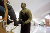 DM0014  Greg Perry shines shoes in the lobby of the Independence Plaza in Denver Tuesday Dec. 16,...