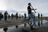 (0563) Members of the Windsor High School Band jump over a puddle as they practice at school in...