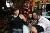 Tattoo artist Jef Kopp colors in a tattoo on Mindy McEachran at Th'ink Tank Tattoo Studio and Art...