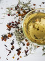 White tea in clear tea cup with assorted loose teas (botanical, green and white) scattered...