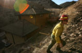 MJM325  A firefighter looks for hot spots behind the Knutson's Lee Hill Rd. home after the Olde...